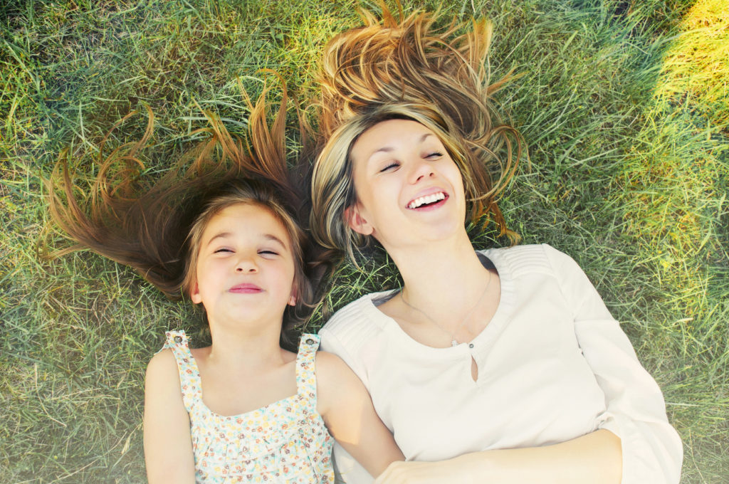 happy little girl and her mother having fun on the grass in sunn